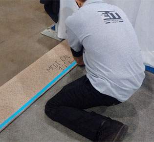 A photo showing staff laying down carpet during a trade show booth installation.